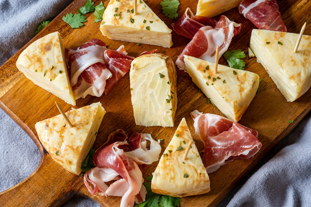 Plate with sliced tortilla espanola and Spanish ham