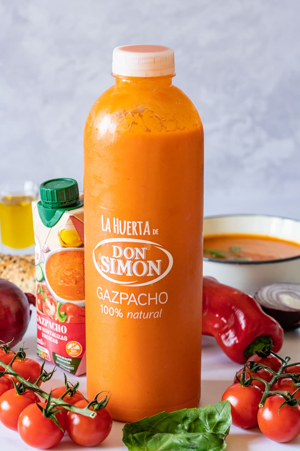 Bottle of gazpacho with fresh tomatoes