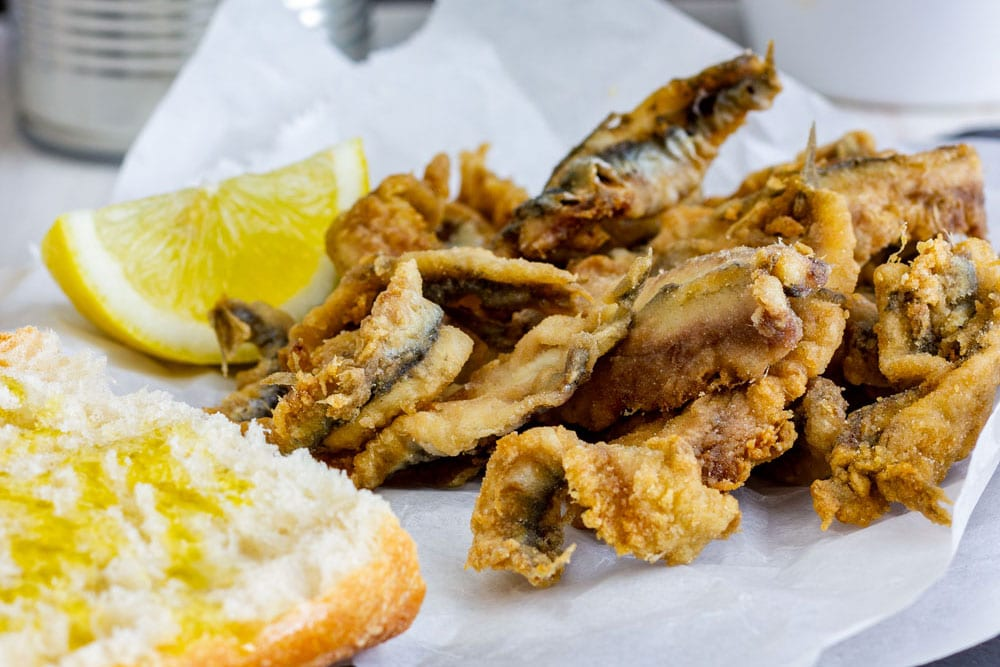 Traditional Spanish tapas fried anchovies with bread and olive oil