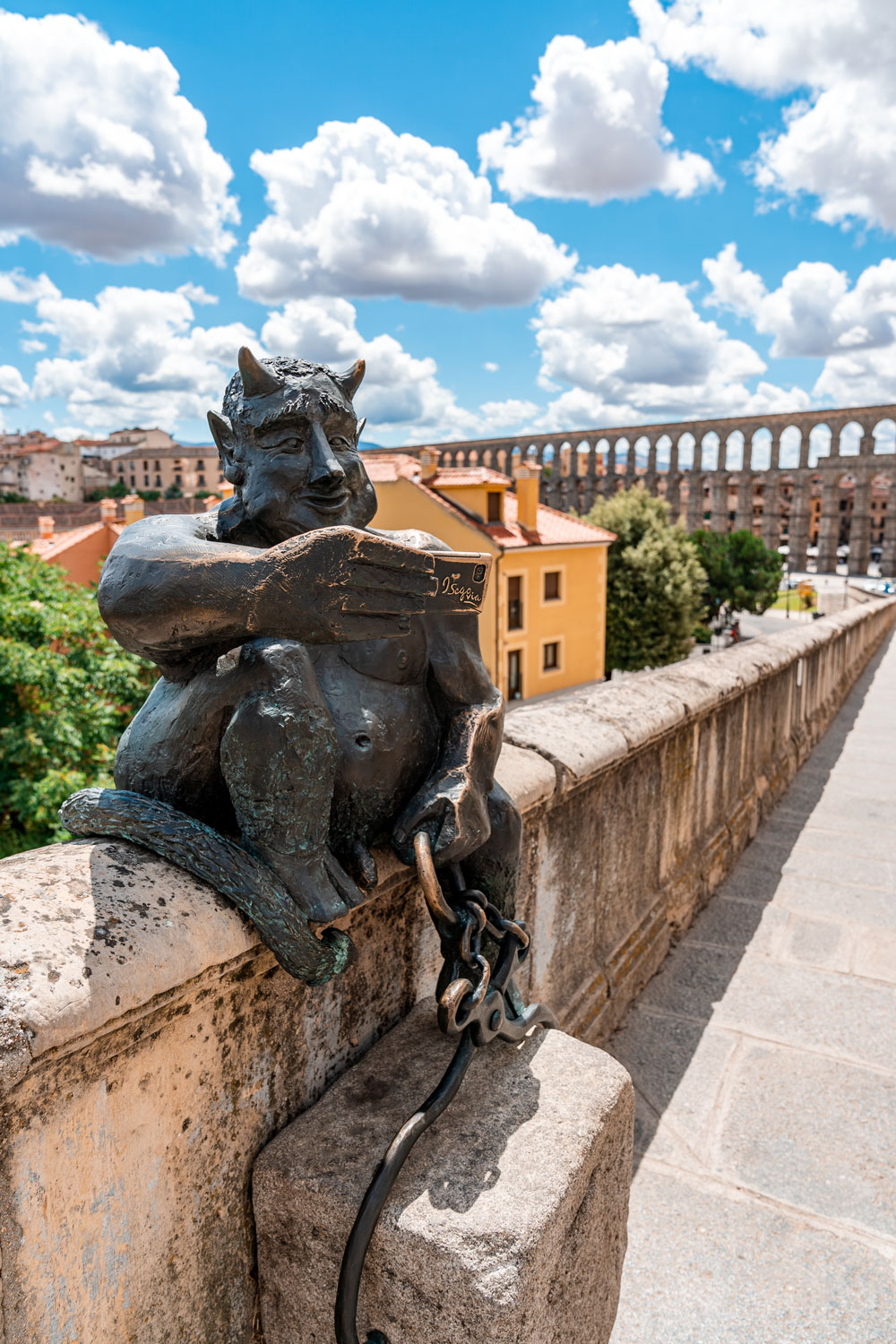 Segovia in a Day - Statue of Devil taking selfie near the Aqueduct